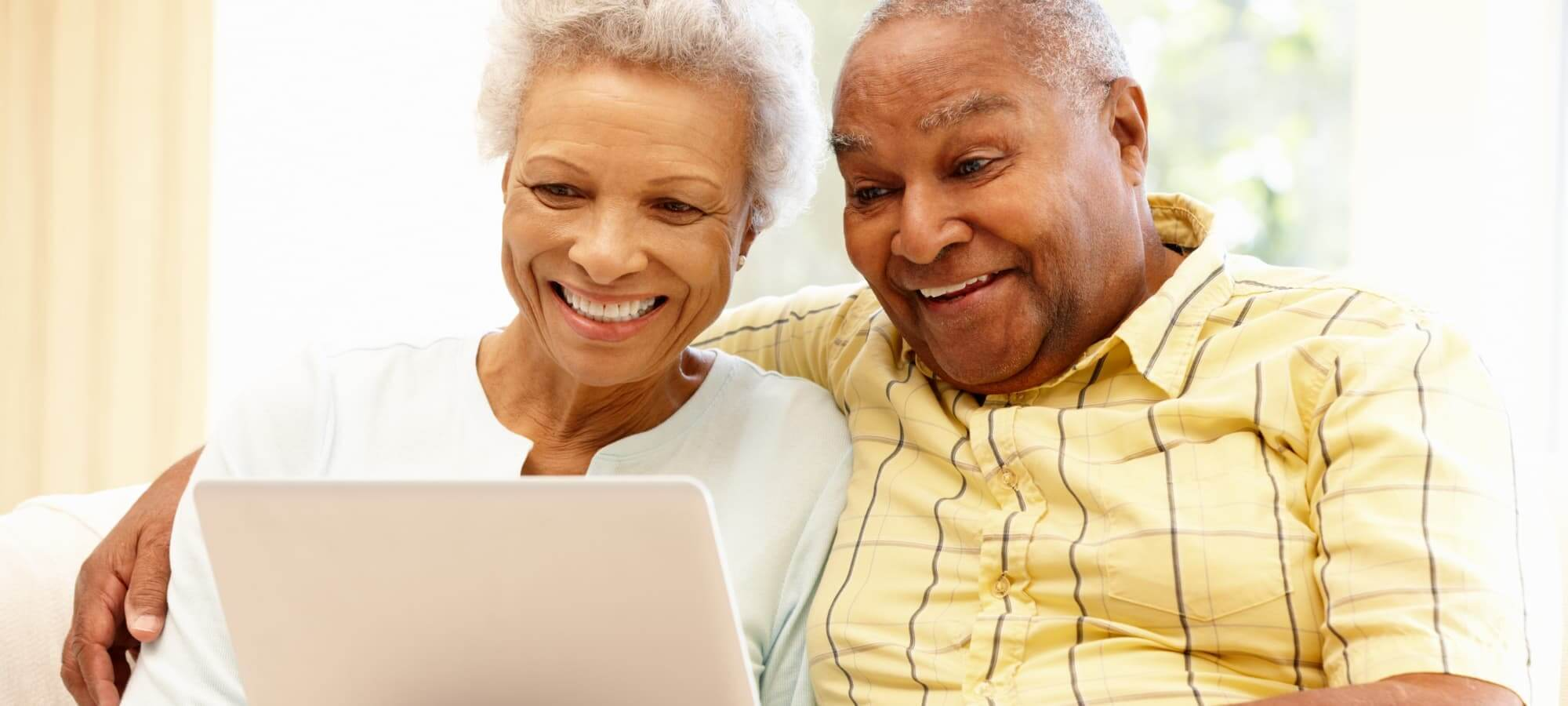 elderly couple watching on their laptop
