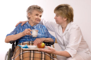 Caregiver assisting on her elderly patient to feed