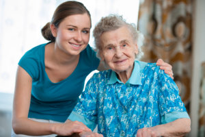 Caregiver smiling with her elderly patient