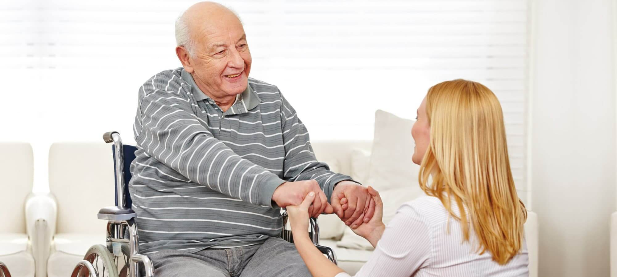 elderly man holding the hand of his caregiver
